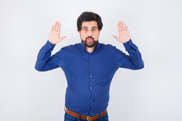 ロイヤルブルーのシャツの正面図で降伏するために手を上げる若い男性。