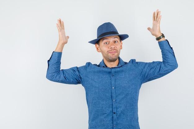 Молодой мужчина поднимает руки в голубой рубашке, шляпе и выглядит счастливым, вид спереди.