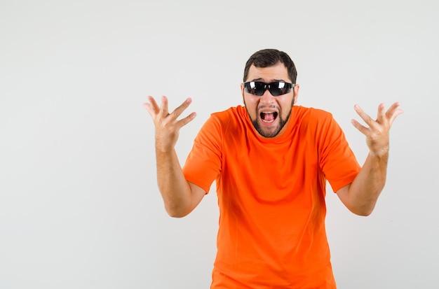 Молодой мужчина поднимает руки в озадаченном жесте в оранжевой футболке и выглядит взволнованным. передний план.
