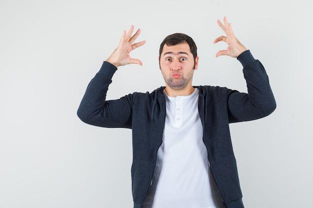 Tシャツ、ジャケット、正面図で困惑したジェスチャーで手を上げる若い男性。