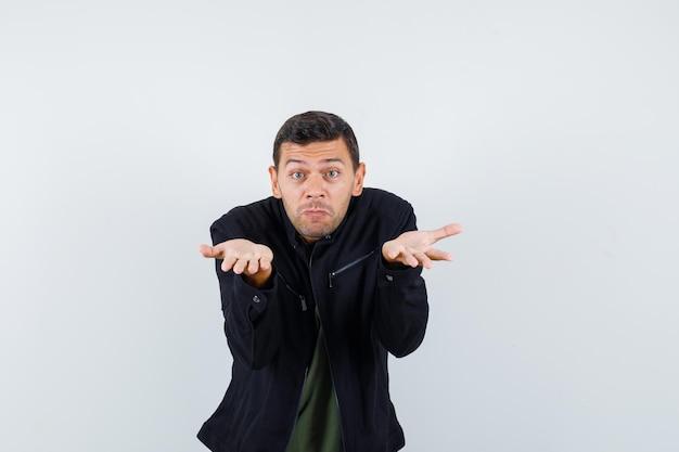 Молодой мужчина поднимает руки в вопросительном жесте в футболке, куртке, вид спереди.