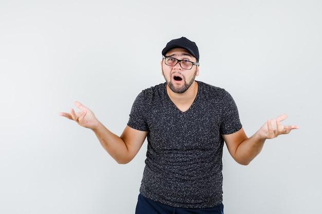 Молодой мужчина в черной футболке и кепке вопросительно поднимает руки и выглядит смущенным