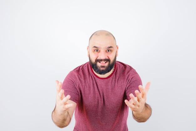 Giovane maschio che alza le mani mentre parla in maglietta rosa e sembra soddisfatto, vista frontale.