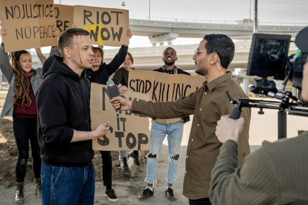 Young male rebel with broken head giving interview to arabian journalist while other protestors waving banners in background
