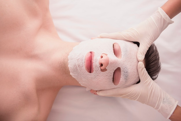 Young male receiving facial mask at beauty salon.