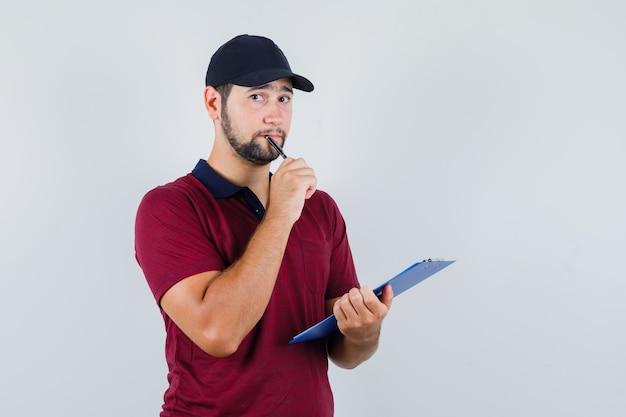 Giovane maschio in maglietta rossa, berretto nero che tiene taccuino e penna e guardando premuroso, vista frontale.