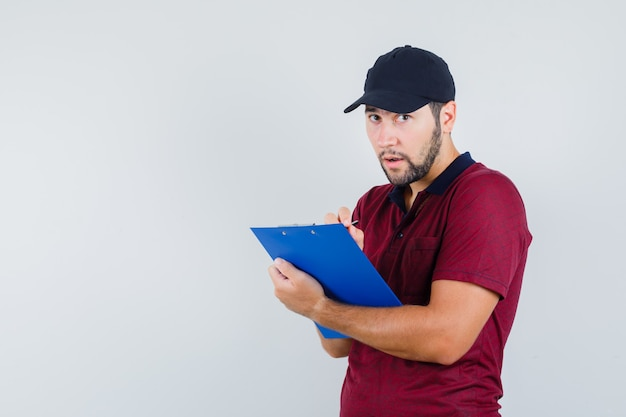 Young male in red t-shirt,black cap looking at camera while writing something on his notebook and looking attentive , front view.