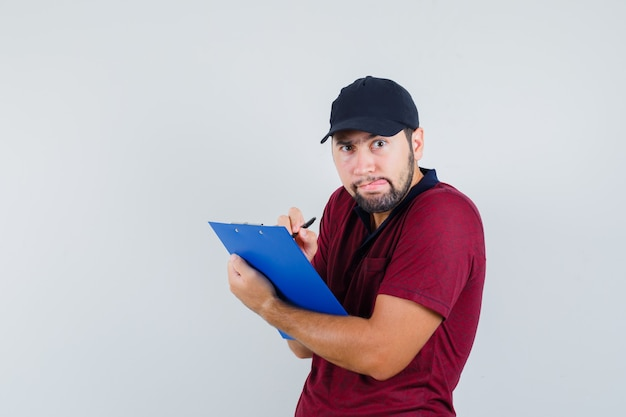 Giovane maschio in maglietta rossa, berretto nero che guarda avanti mentre scrive qualcosa sul suo taccuino e guarda vigile, vista frontale.