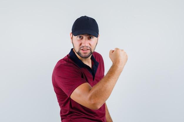Giovane maschio in maglietta rossa, berretto nero che mostra il suo potere e sembra nervoso, vista frontale.