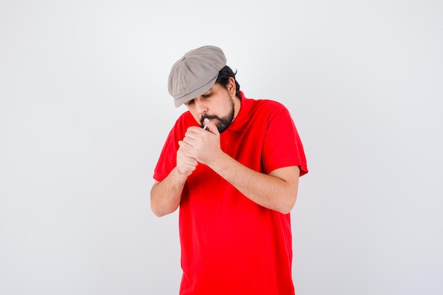 Young male in red t-shirt,cap smoking , front view.