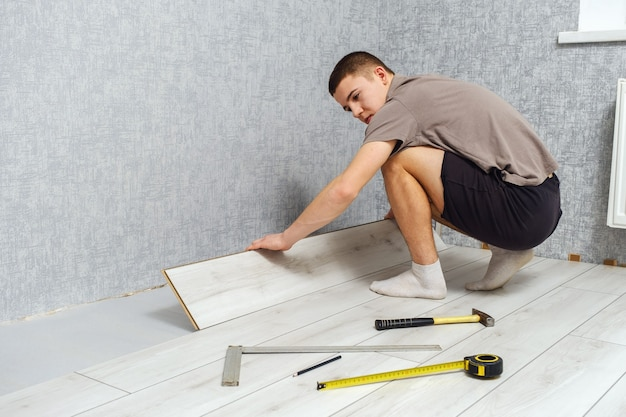 Young male repairman is laying wooden panel of laminate floor indoors on the knees. laminate flooring, copy space, back view