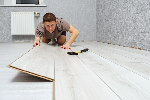 Young male repairman is laying wooden panel of laminate floor indoors. laminate flooring, copy space. selective focus