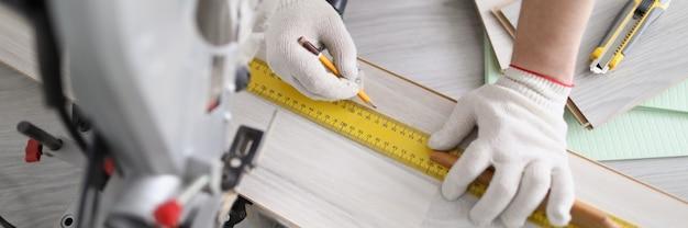 Молодой мужчина-ремонтник делает разметку деревянной панели карандашом и линейкой перед резкой