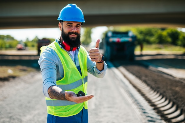 彼の仕事の若い男性の道路建設労働者。明るい晴れた日。強い光。