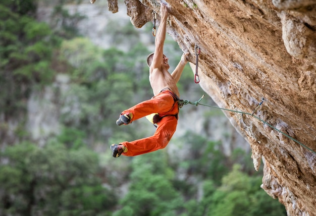 Young male rock climber after jumping and gripping small handholds on overhanging cliff