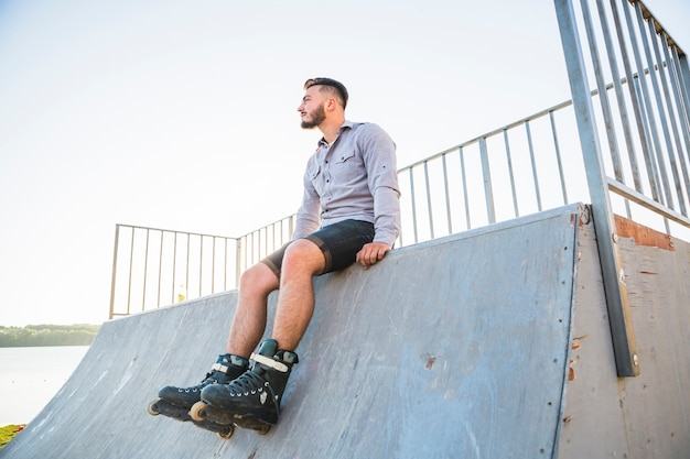 Young male rollerskater sitting in skate park