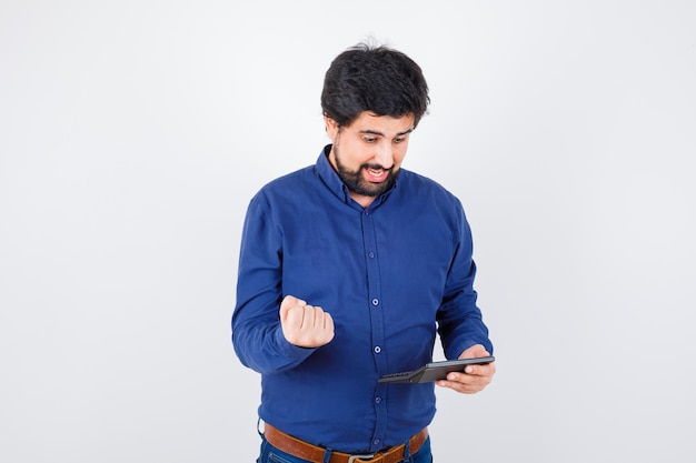 Young male in royal blue shirt calculating while showing success gesture and looking happy , front view.