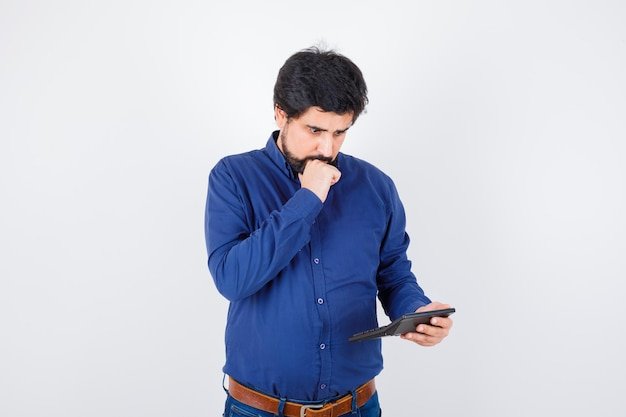 Young male in royal blue shirt calculating while thinking , front view.