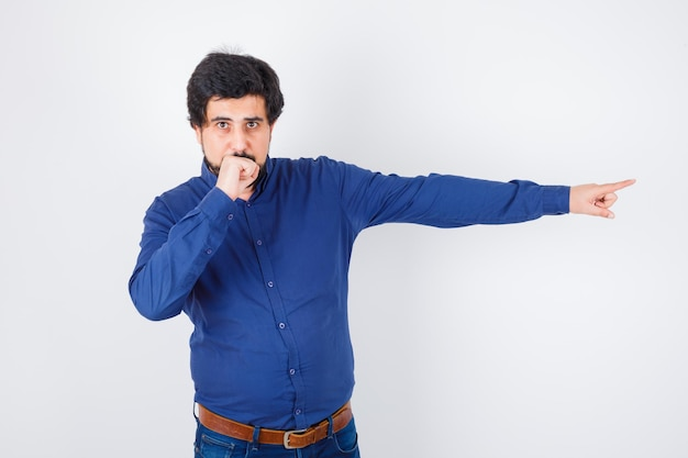 Young male in royal blue shirt pointing away with fist on mouth and looking troubled , front view.