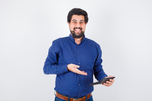 Young male in royal blue shirt showing calculator while laughing , front view.