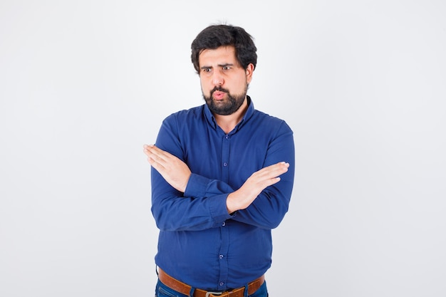 Young male in royal blue shirt showing closed gesture , front view.