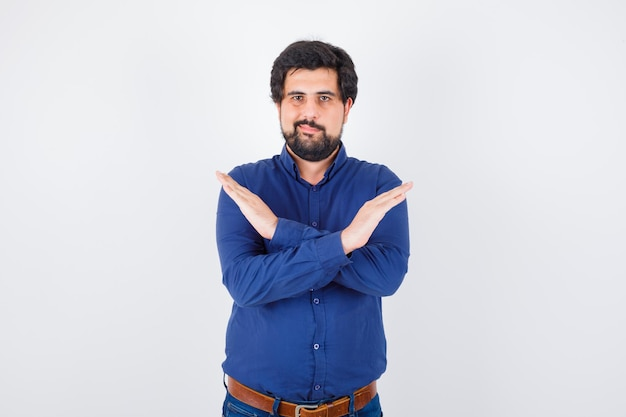 Young male in royal blue shirt showing closed gesture and looking confident , front view.