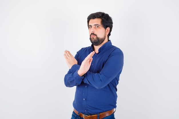 Young male in royal blue shirt showing closed gesture and looking serious , front view.