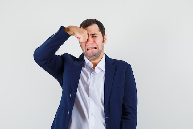 Young male rubbing eye while crying in shirt, jacket and looking offended