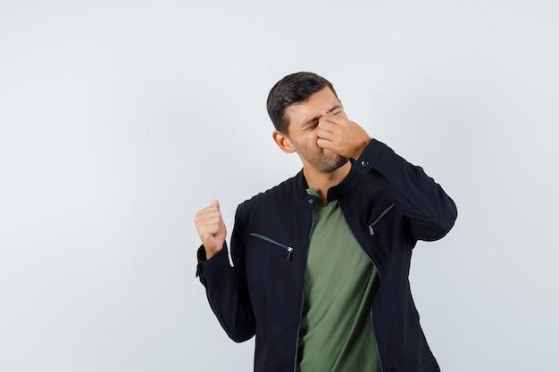 Молодой мужчина протирает глаза и нос в футболке, куртке и выглядит усталым, вид спереди.