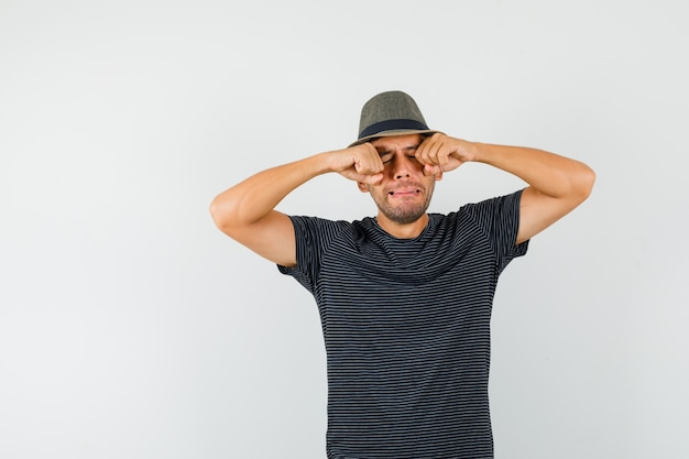 Young male rubbing eyes while crying in t-shirt hat and looking offended