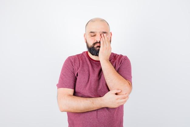 Молодой мужчина в розовой футболке потирает один глаз и выглядит сонным. передний план.