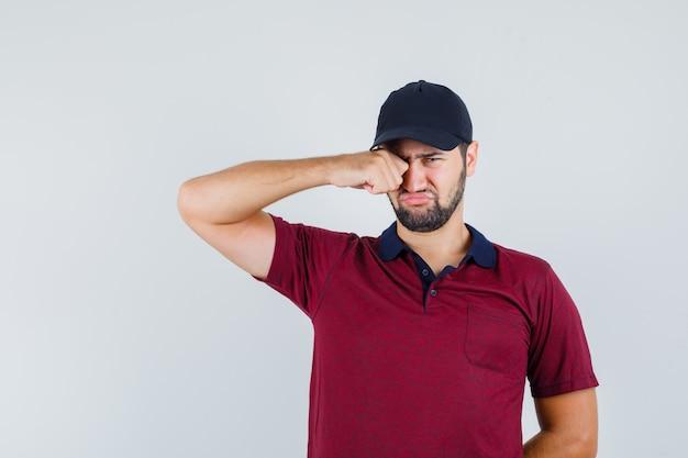 Giovane maschio strofinando il suo occhio in maglietta rossa, berretto nero e guardando triste, vista frontale.