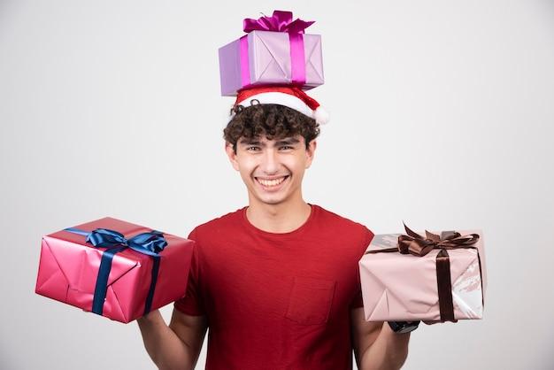 Giovane maschio in cappello della santa che tiene mazzo di regali.