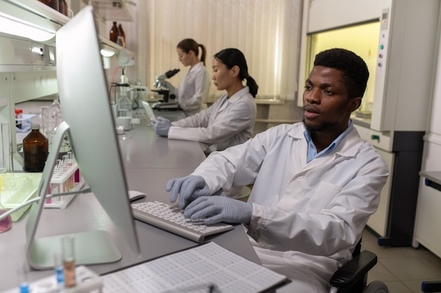 Young male scientist in gloves and whitecoat sitting in front of computer screen in lab