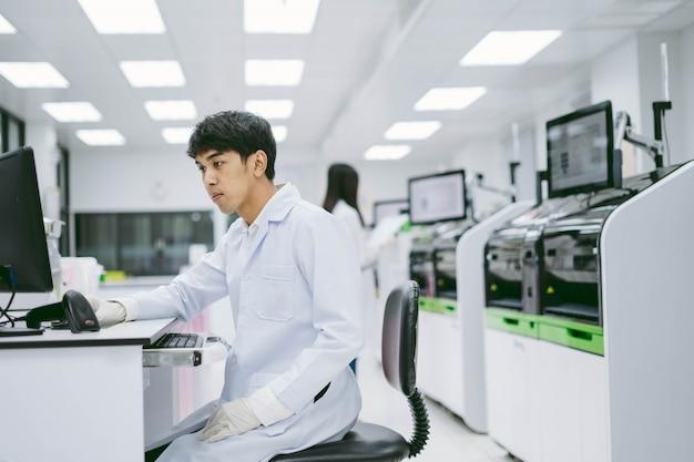 コンピューターで自動化された血液アナライザーレポートから結果を探している若い男性の科学者