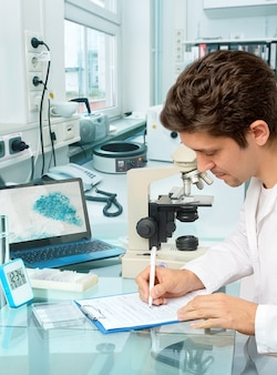 Young male scientist or tech makes notes in histopathology laboratory