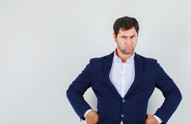 スーツを着て腰に手を顔をしかめ、暗い、正面図を見て若い男性。