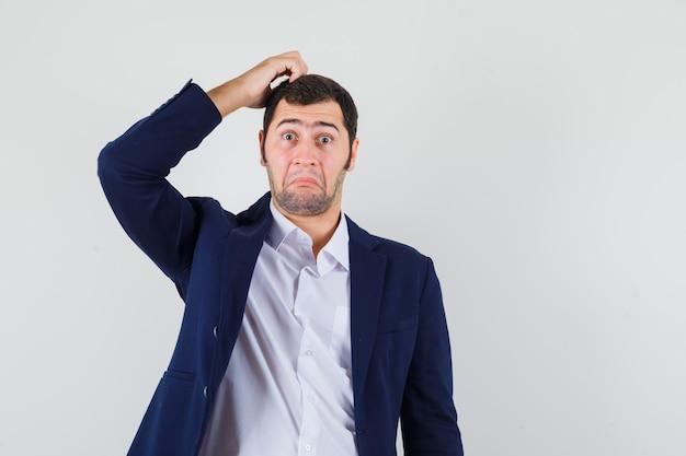 Молодой мужчина почесывает голову в рубашке, куртке и выглядит нерешительно
