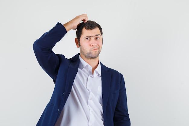 Молодой мужчина почесывает голову в рубашке, куртке и выглядит задумчивым
