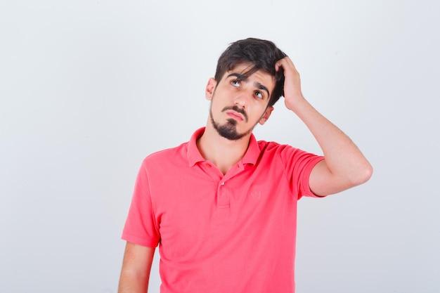 若い男性がtシャツを着て頭を掻き、思慮深く見える、正面図。