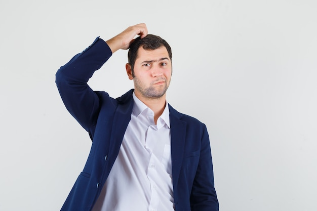 Young male scratching head in shirt, jacket and looking pensive