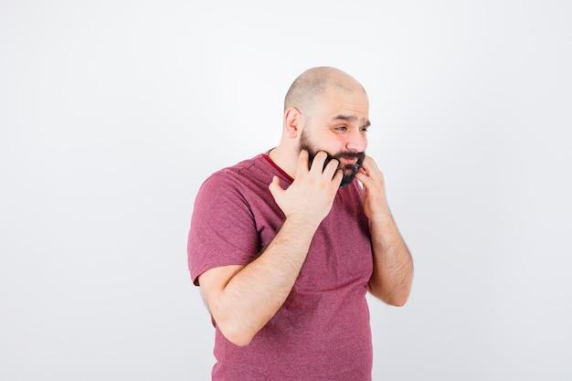 Молодой мужчина почесывает бороду в розовой футболке и выглядит обеспокоенным, вид спереди.