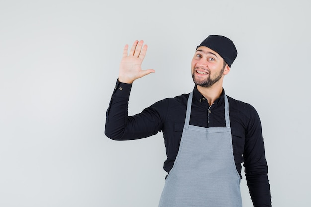 Young male in shirt, apron waving hand to say hello or goodbye and looking merry , front view.