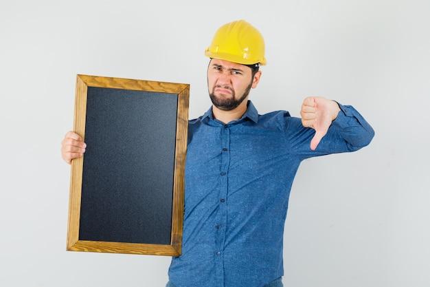 Giovane maschio in camicia, casco che tiene lavagna, che mostra il pollice verso il basso e sembra scontento, vista frontale.