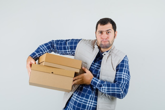 Young male in shirt,jacket carrying boxes and looking uncomfortable , front view.