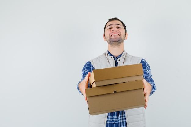 Giovane maschio in camicia, giacca dando scatole a qualcuno e guardando soddisfatto, vista frontale.