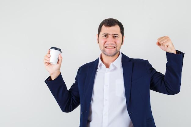 Giovane maschio in camicia, giacca che tiene tazza di caffè e sembra fortunato