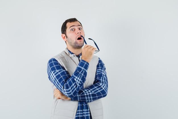Giovane maschio in camicia, giacca con gli occhiali mentre pensa e guarda pensieroso, vista frontale.