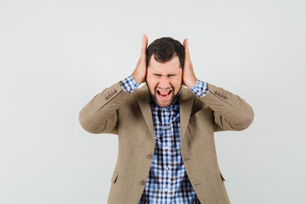 Giovane maschio in camicia, giacca tenendo le mani sulle orecchie e guardando irritato, vista frontale.