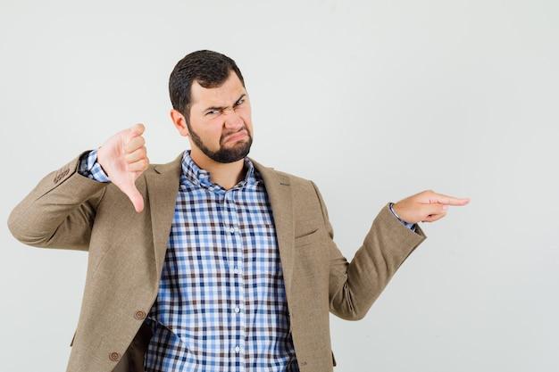 Giovane maschio in camicia, giacca che punta di lato, che mostra il pollice verso il basso e sembra insoddisfatto, vista frontale.